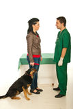 Owner with dog visiting vet doctor. Owner women with her dog having conversation with vet male doctor in his office Royalty Free Stock Images