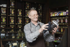 Owner Dusting Jar Of Tea. Senior tea shop owner dusting jar of tea stock photography