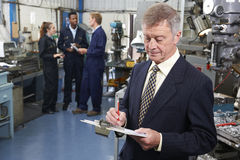 Owner Of Engineering Factory With Staff In Background Royalty Free Stock Images