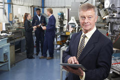 Owner Of Engineering Factory Using Digital Tablet With Staff In. Owner Of Engineering Factory Using Digital Tablet stock image