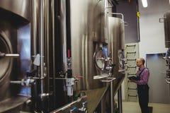 Owner examining machinery at brewery Stock Image