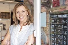 Owner Of Gift Shop Standing In Doorway. Smiling Owner Of Gift Shop Standing In Doorway Royalty Free Stock Images