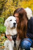 Owner girl and her golden retriever hugging outdoors. Girl staying with her golden retriever dog outdoors, hugging and showing love and tenderness Royalty Free Stock Images