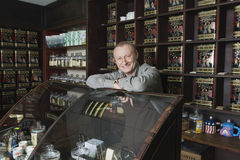 Owner Leaning On Display Cabinet In Shop Royalty Free Stock Photos
