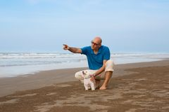 Owner with dog pointing to something at the beach. Owner with Maltese dog pointing to something at the beach Royalty Free Stock Photo