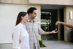 Owner of a new apartment: Couple receiving keys Stock Photography