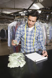 Owner With Notepad Analyzing Receipts At Counter Royalty Free Stock Photos