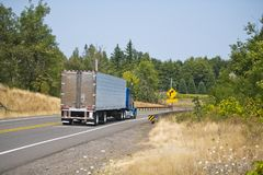 Blue big rig semi truck with refer semi trailer running on winding green highway for delivery. Owner - operators are the main core of the drivers of classic big royalty free stock images