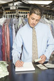Owner With Receipts And Banknotes Analyzing Accounts At Counter. Young laundry owner with receipts and banknotes analyzing accounts at counter Royalty Free Stock Photos