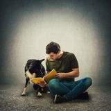 Owner seated on floor training his cute puppy reading together an interesting book. Curious purebred border collie dog and his master reading together an stock images