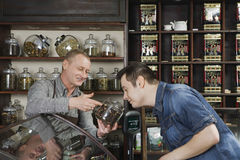 Owner Showing Coffee Jar To Customer Shop. Senior male owner showing tea jar to customer shop stock photo