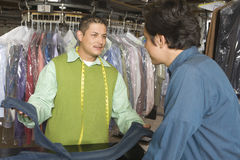 Owner Showing Dry Cleaned Jeans To Customer In Laundry Stock Photos