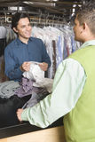 Owner Showing Dry Cleaned Shirts To Customer At Counter Royalty Free Stock Photos