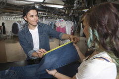 Owner Showing Jeans Measurement To Client In Laundry. Male owner showing jeans measurement to female client in laundry Stock Photography