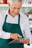 Owner Using Digital Tablet In Grocery Store Stock Photo