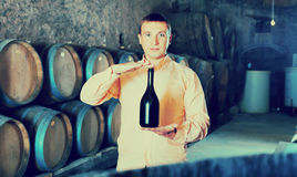 Owner of winery showing bottle of wine. In factory cellar Stock Image