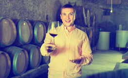 Owner of winery standing with wine in   cellar. Cheerful friendly smiling owner of winery standing with wine in wooden barrels cellar Stock Image