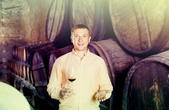 Owner of winery standing with wine in   cellar. Cheerful owner of winery standing with wine in wooden barrels cellar Stock Image