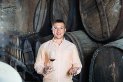 Owner of winery standing with wine in   cellar. Cheerful owner of winery standing with wine in wooden barrels cellar Royalty Free Stock Photo
