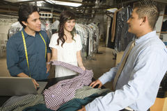 Owners Showing Dry Cleaned Clothes To Customer In Laundry Royalty Free Stock Photos