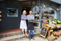 Owners Standing Next To Produce Display At Deli Royalty Free Stock Image