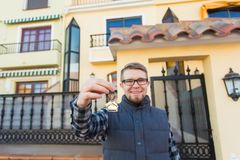 Ownership, real estate, property and tenant concept - Portrait of a cheerful young man holding key from new home royalty free stock photography