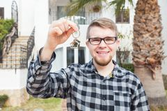 Ownership, real estate, property and tenant concept - Portrait of a cheerful young man holding key from new home royalty free stock image