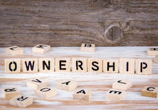 Ownership from wooden letters. On wooden background Stock Image