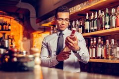 Handsome man in glasses owning bar holding bottle of cognac. Owning bar. Handsome dark-haired rich man in glasses owning bar holding bottle of cognac royalty free stock photo