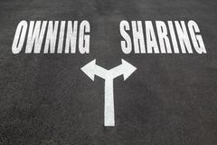 Owning vs sharing choice concept. Two direction arrows on asphalt Stock Image