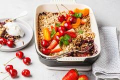 Owoc i jagoda owies rozdrobnią w piekarnika naczyniu na szarym tle zdjęcie royalty free