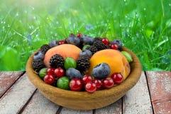 Owoc i jagody w drewnianym talerzu, agrest, czernica Zdjęcie Royalty Free
