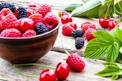 Owoc i jagody w pucharze na drewnianym tle Dojrzała malinka, wiśnia, morwa zdjęcie stock
