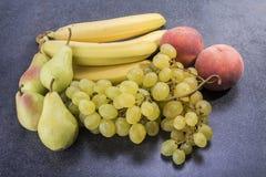 Owoc na górze kuchennych bananów stołowych winogron brzoskwini grochu i Fotografia Stock