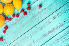Owoc na nieociosanym błękita stole, cytrynach, winogronach i czerwieni jagodach, obraz royalty free