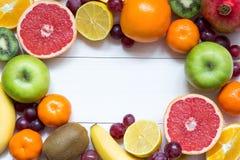 Owoc ramowy tło z pomarańczami, tangerines, banan, jabłko, cytryna na białym drewnianym stole, zdrowa jedzenie rama fotografia royalty free