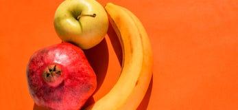 Owoc ustawiać: jabłko, banan i granatowiec z lewej strony pomarańczowego tła, Fotografia Royalty Free