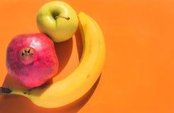 Owoc ustawiać: jabłko, banan i granatowiec z lewej strony pomarańczowego tła, Zdjęcia Stock