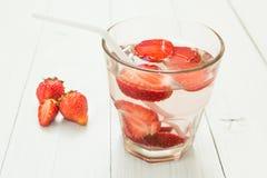 Owoc woda w szkle na białym stole truskawka organicznych obrazy stock