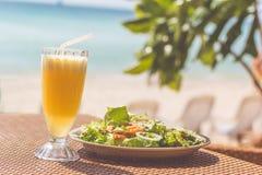Owoce morza sałatka, pomarańczowy świeży sok na stołowym pobliskim morzu Fotografia Stock