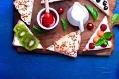 Owocowa grzanka na drewnianej desce na błękitnym nieociosanym tle Zdrowy śniadaniowy Czysty łasowanie około tło bow puste pojęcia Fotografia Royalty Free