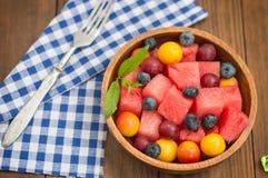 Owocowa i jagodowa sałatka arbuz, czarne jagody, śliwki, rodzynki, agrest, czereśniowa śliwka Drewniany tło Odgórny widok Zdjęcie Royalty Free