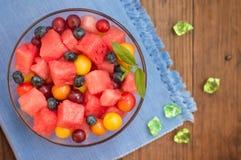 Owocowa i jagodowa sałatka arbuz, czarne jagody, śliwki, rodzynki, agrest, czereśniowa śliwka Drewniany tło Odgórny widok Obraz Royalty Free