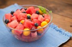 Owocowa i jagodowa sałatka arbuz, czarne jagody, śliwki, rodzynki, agrest, czereśniowa śliwka Drewniany tło Odgórny widok Zdjęcia Stock