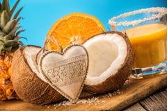 Owocowi ananasowi smooties z koksem i pomarańcze na drewnianym stole z sercem Zdjęcie Stock