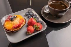 Owocowi tartlets na talerzu drewnianym fili?anka kawy na stole i, owoc piec skorupa, owocowa babeczka z jagod? obraz royalty free