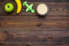 Owocowy puree dla dziecka Zgrzyta z jedzeniem, jabłko, banan, zabawki na ciemnej drewnianej tło odgórnego widoku kopii przestrzen Zdjęcie Stock