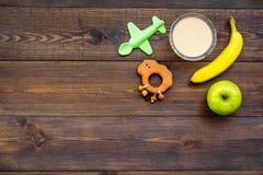 Owocowy puree dla dziecka Zgrzyta z jedzeniem, jabłko, banan, zabawki na ciemnej drewnianej tło odgórnego widoku kopii przestrzen Obrazy Stock