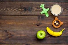 Owocowy puree dla dziecka Zgrzyta z jedzeniem, jabłko, banan, zabawki na ciemnej drewnianej tło odgórnego widoku kopii przestrzen Zdjęcia Stock