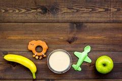 Owocowy puree dla dziecka Zgrzyta z jedzeniem, jabłko, banan, zabawki na ciemnej drewnianej tło odgórnego widoku kopii przestrzen Obraz Royalty Free